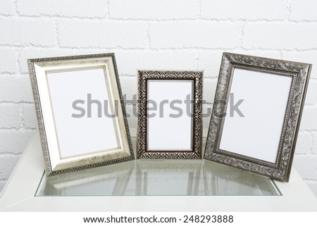 Photo frames on coffee table on brick wall background - stock photo