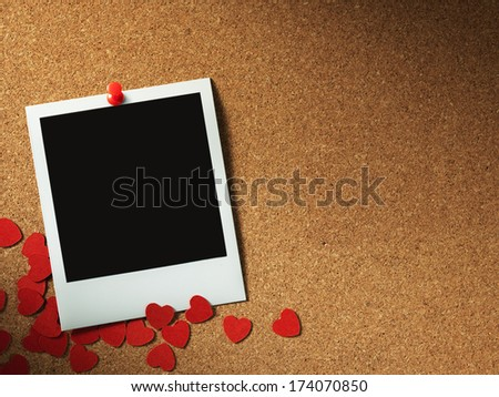 photo frames on corkboard with paper heart - stock photo
