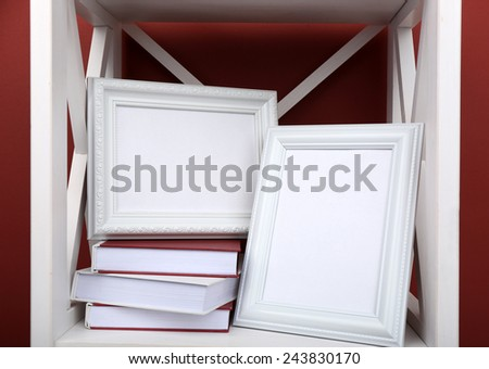Photo frames with books on shelf, on color wall background - stock photo