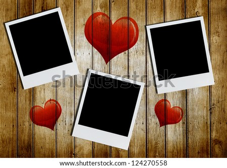 Photo frames with heart shape on old wooden background - stock photo