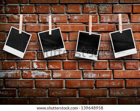 Photo frames with pins on rope over old aged brick wall - stock photo