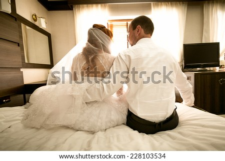 Photo from back of bride and groom sitting on bed and hugging - stock photo