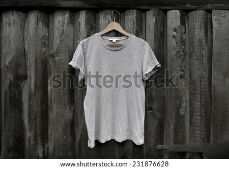 Photo gray blank t-shirt on dark wood wall - stock photo