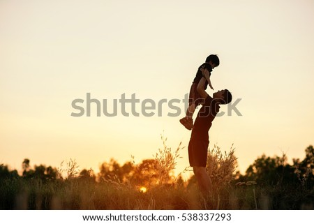 photo happy joyful father having fun throws up in the air child, family, travel, vacation, father's day - concept. Sunlight on the sunset