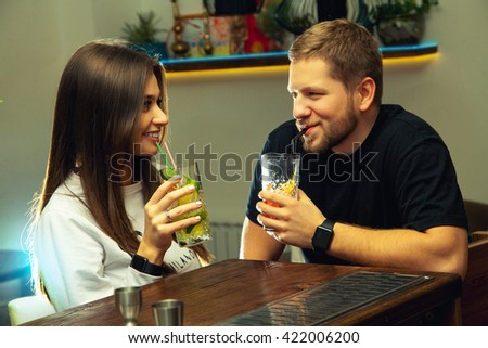 Photo horizontal of sexy young couple flirting at the bar and drinks cocktails. night life concept