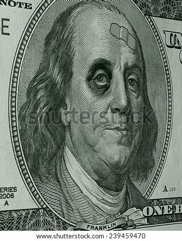 Photo Illustration of Ben Franklin on a hundred dollar bill, sporting a black eye and a band-aid, as the weak dollar takes a beating.