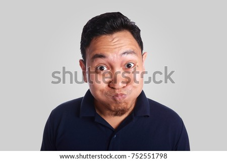 Photo image of funny Asian man mocking face trying not to laugh