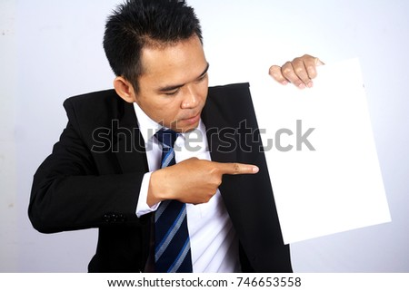Photo Image of handsome asian businessman holding a blank paper with pointing gesture
