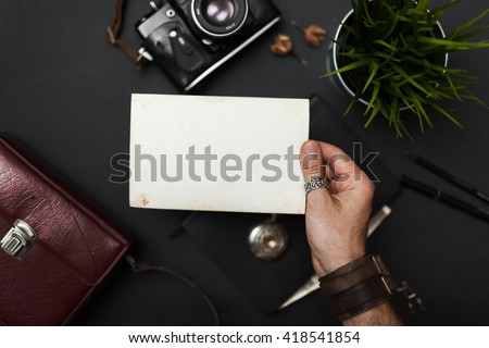 Photo in the hand, vintage style, on the black table, frame