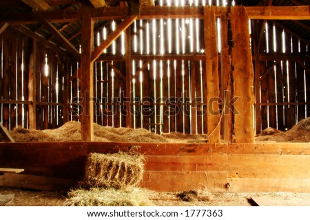 Photo inside a barn with light streaming in through siding.