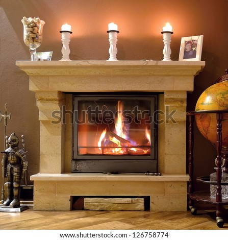 Photo interior of a home with a burning fireplace, candles and decorations.  Ready for gifts for Christmas.