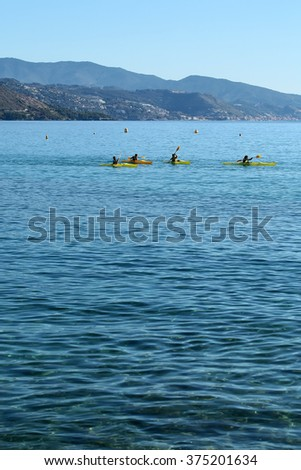 Photo long shot of group of people rowing yellow canoes paddling in beautiful clear calm blue sea with ripples pebble seabed seaside mountains summer day on seascape background, vertical picture