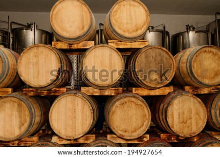 Photo lots of wooden barrel in a winery - stock photo