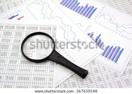 Photo magnifier with graphs and figures in the tables  - stock photo