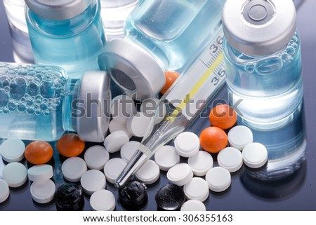 Photo medical vials for storage of medicines on a black mirrored background with bright reflections. Pills.