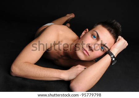 Photo model laying on the floor on black background - stock photo