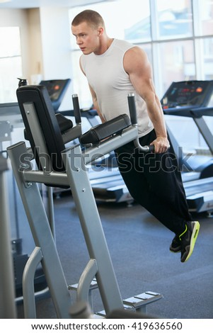 Photo muscular man is engaged on the bars
