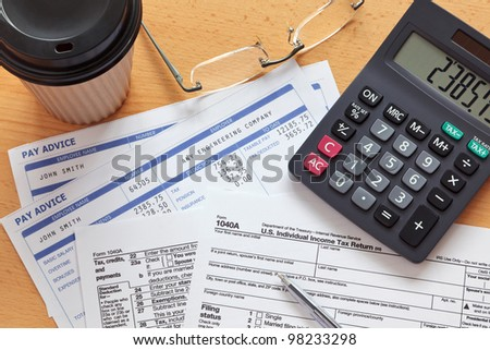 Photo of a 1040A tax form with payslips and a calculator.The payslip is a mock up the names and all other information on it is fictional.