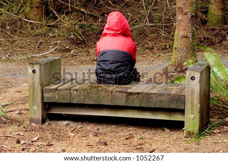 Photo of a an unhappy boy in a red coat sitting on a bench at Gnat Creek