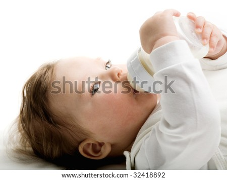 Photo of a baby drinking milk from the bottle - stock photo