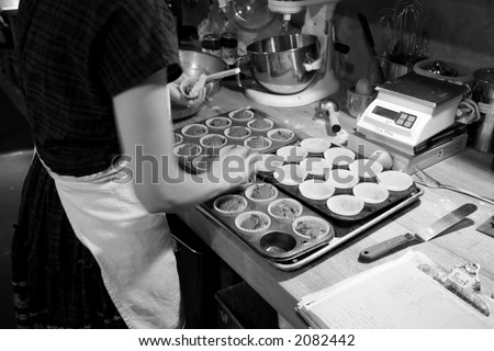 Photo of a baker making chocolate muffins in an organic bakery.