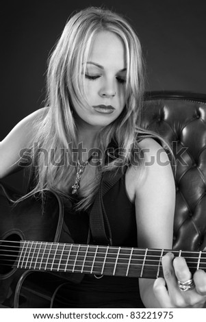 Photo of a beautiful blond female playing an acoustic guitar.