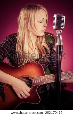 Photo of a beautiful blond woman playing an acoustic guitar. Filtered to have a vintage look.
