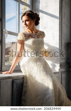 photo of a beautiful brunette bride in a luxurious wedding dress sitting near window in elegant expensive interior - stock photo