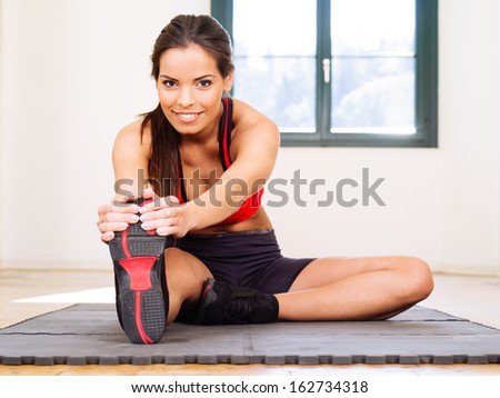 Photo of a beautiful female stretching on the floor sitting on a mat.  - stock photo