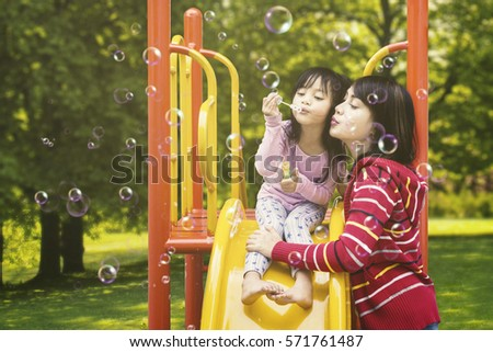 Photo of a beautiful mother and her daughter blowing soap bubbles on the playground at the park