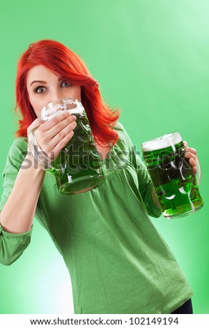 Photo of a beautiful redhead holding two huge mugs of green beer and drinking from one, on St. Patricks Day. - stock photo