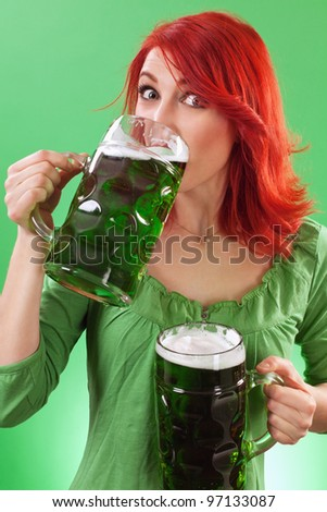 Photo of a beautiful redhead holding two huge mugs of green beer and drinking from one, on St. Patricks Day.