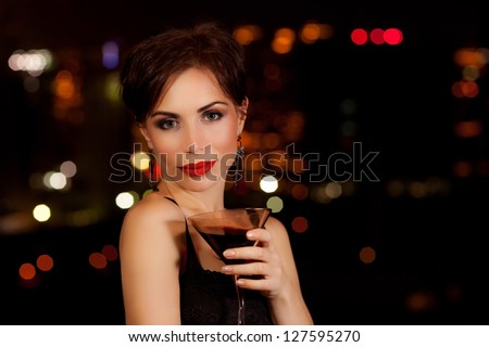 Photo of a beautiful woman having martini in outdoor restaurant, celebration party, city nightlife lifestyle, glamorous lady with drink, female enjoying cocktail - stock photo