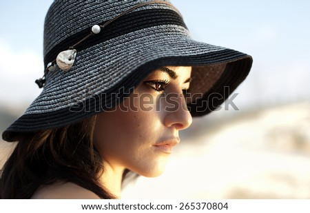 Photo of a beautiful woman in black stylish hat, closeup portrait of gorgeous young lady with natural makeup, side view of lovely charming Arabic female outdoor - stock photo