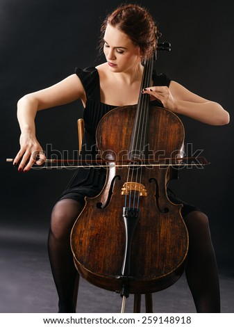 Photo of a beautiful woman playing an old cello. - stock photo