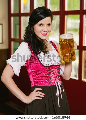 Photo of a beautiful woman wearing traditional dirndl and drinking a huge beer. - stock photo