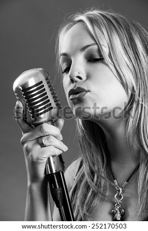 Photo of a beautiful young blond singing into a vintage microphone done in black and white.