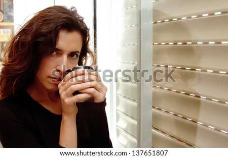 Photo of a beautiful young female drinking coffee and looking out the window