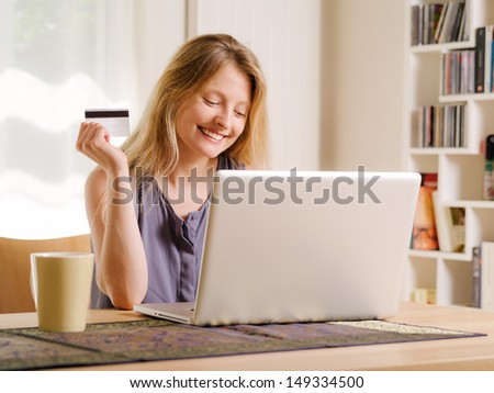 Photo of a beautiful young female shopping online and paying with a credit card. Credit card information is fictitious. - stock photo