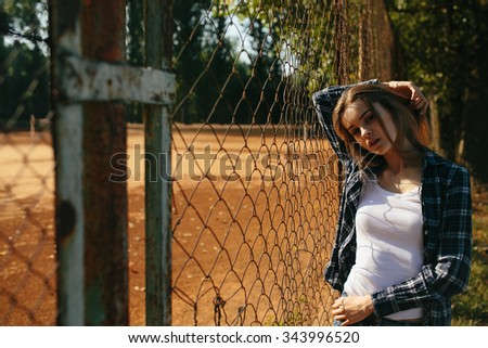 Photo of a beautiful young girl near the tennis courts