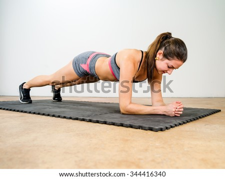 Photo of a beautiful young woman exercising and doing an elbow plank to strengthen her stomach muscles. - stock photo