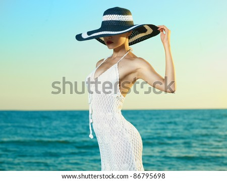 Photo of a beautiful young woman in a hat by the sea