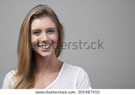 Photo of a beautiful young woman smiling cheerfully. Studio shot - stock photo