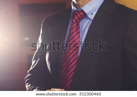 Photo of a black  suit with blue shirt and red and blue patterned tie