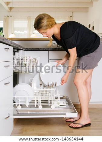Photo of a blond female leaning over and unloading her dishwasher. - stock photo
