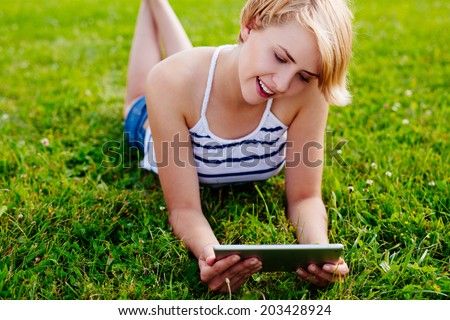 Photo of a blond pretty woman lying on the grass and browsing websites on her tablet - stock photo