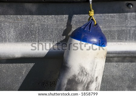 Photo of a blue and white float hanging from a fishing boat. - stock photo