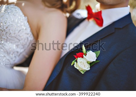 Photo of a blue suit with white shirt and red tie. The bride next to the groom - stock photo