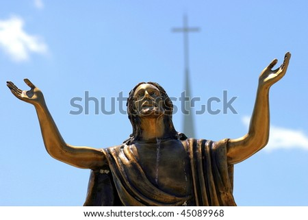 Photo of a bronze statue of Jesus looking at the sky with both arms up.