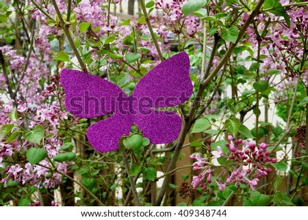 Photo of a butterfly made of glittery purple paper on a blooming lilac bush. Creativity concept. Craft butterfly in garden. Glittery paper butterfly. Spring concept. Unusual butterfly & lilac flowers. - stock photo